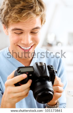Joyful young photographer taking pictures using digital camera d