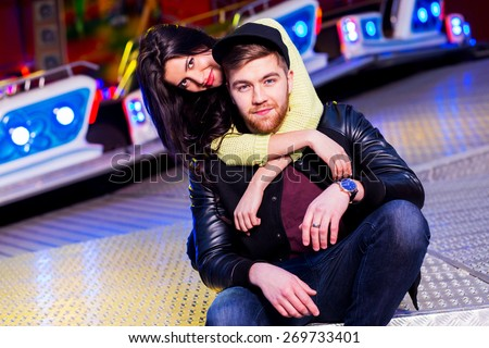 Joyful young stylish  couple being playful while visiting an attractions park arcade with rides. Have fun , enjoying  their time. Wearing spring trendy  outfit , neon sweater and swag hat. - stock photo