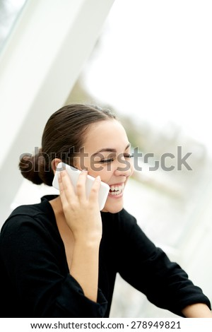 Joyful young woman chatting on her mobile phone laughing as she listens to the conversation, side view seated indoors - stock photo