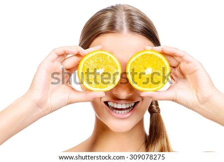 Joyful young woman holding juicy oranges before her eyes. Healthy eating concept. Diet. Isolated over white.  - stock photo