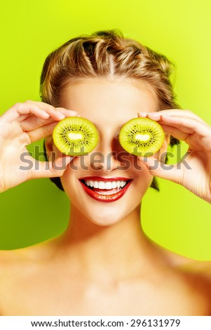 Joyful young woman holding kiwi before her eyes. Green background. Tropical fruits. Healthy eating. Beauty, cosmetics. - stock photo