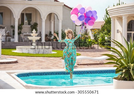 Joyful young woman jumping into the pool while holding a bunch of balloons  - stock photo