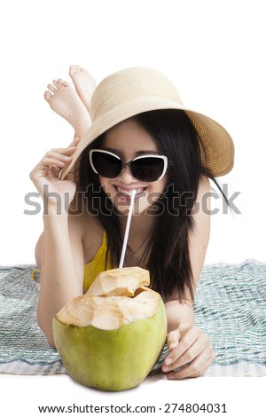 Joyful young woman lying on the mat while wearing swimsuit, hat, and sunglasses. enjoy coconut water, isolated on white - stock photo