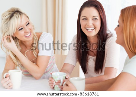 Joyful young Women sitting at a table with cups in a kitchen