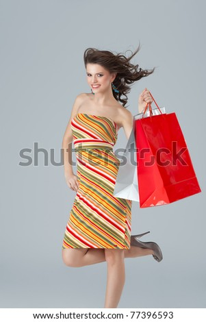 joyfull brunette carrying shopping bags wind blowing - stock photo