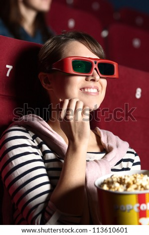 Joyfull woman is watching a movie at the cinema - stock photo