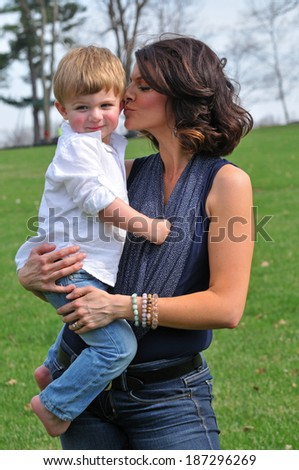 joyfull young mother kissing her little boy on the cheek - stock photo