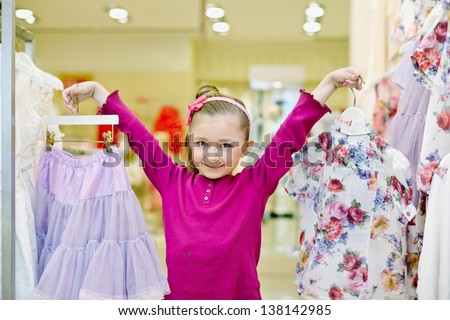 Joyfully smiling little girl shows hangers with light-violet skirt and flower-patterned blouse - stock photo