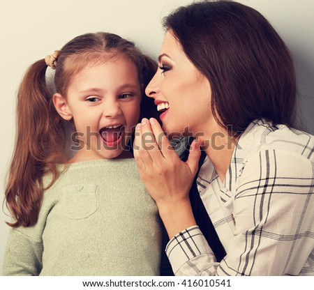 Joying young mother whispering the secret to her funny grimacing daughter in ear in studio. Toned closeup portrait - stock photo