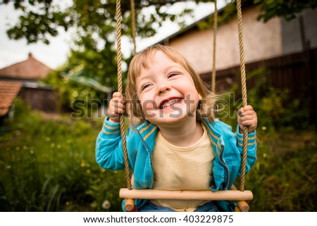 Joyous child swinging on seesaw in backyard - stock photo