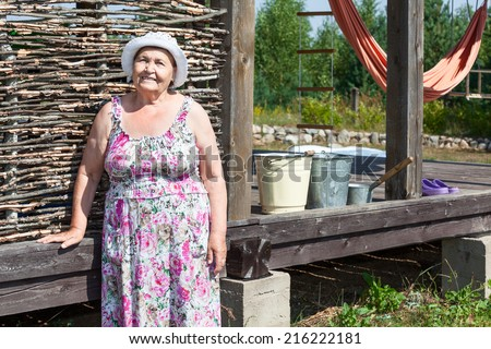 Joyous senior woman standing near house wall - stock photo