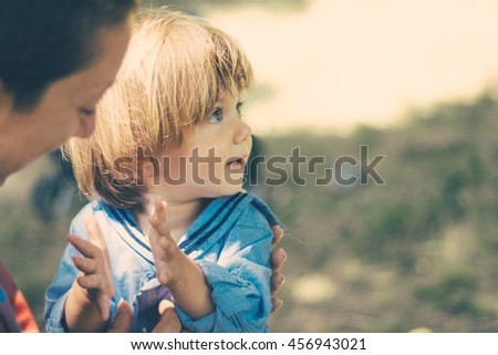 Joyous young woman and charming blond kid, in the natural environment - stock photo