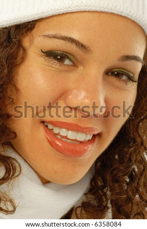 Joyous young woman in winter cap and scarf laughing, full of exuberance and cheer - stock photo
