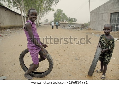 JUBA, SOUTH SUDAN - FEBRUARY 26: Unidentified kids play on a street of Juba on February 26, 2012 in Juba, South Sudan. Juba is full of refugees who live with their children in appalling conditions. - stock photo
