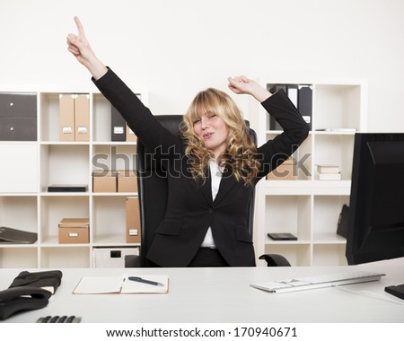 Jubilant businesswoman celebrating a success pointing and punching the air with her fist as she sits at ger desk in the office
