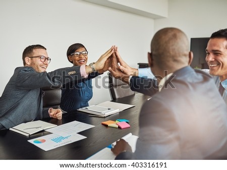Jubilant multiracial business team cheering and laughing as they congratulate each other with a high fives hand gesture - stock photo