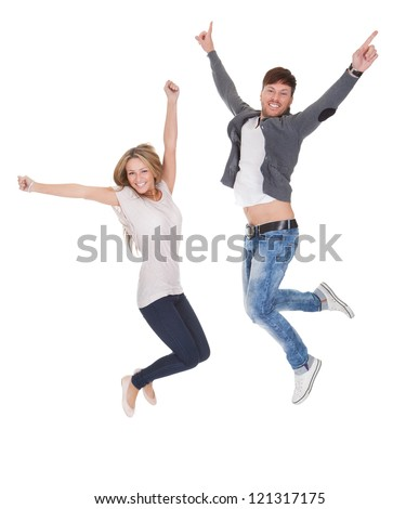Jubilant young man and woman leaping high in the air for joy with their arms raised isolated on white - stock photo