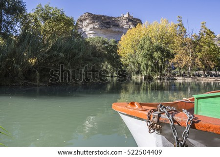 Jucar river, boat of recreation in small lagoon in the central part of the town, at the top of mountain limestone is situated castle of Almohad origin of the century XII, Alcala del Jucar, Spain