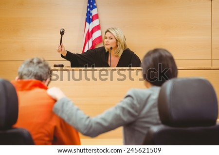 Judge about to bang gavel on sounding block in the court room - stock photo
