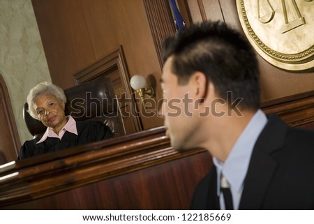 Judge and lawyer looking at each other in courtroom - stock photo