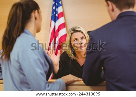 Judge and lawyers speaking in front of the american flag in the court room - stock photo