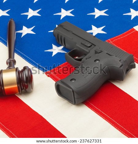 Judge gavel and gun over USA flag - self-defense law concept - stock photo