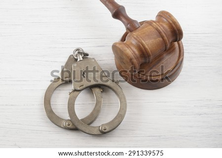 Judge gavel and handcuffs on white table, court concept - stock photo
