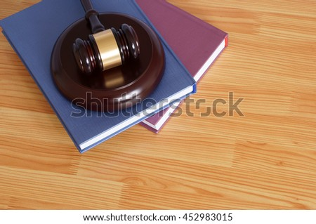 Judge gavel and legal books on wooden table, legal system concept
