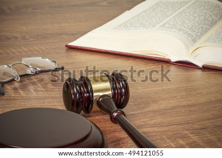 Judge gavel and old books on a wooden table
