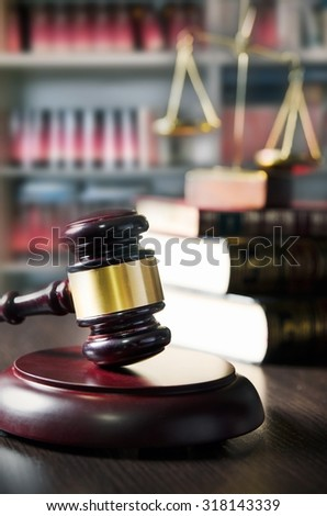 Judge gavel and scale in court. Library with lot of books in background - stock photo