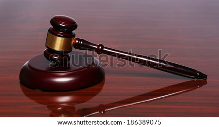 Judge gavel and sound board on the polished table - stock photo