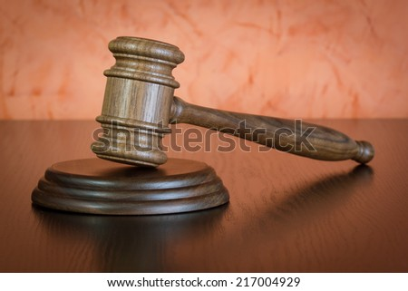 Judge gavel on brown wooden table - stock photo