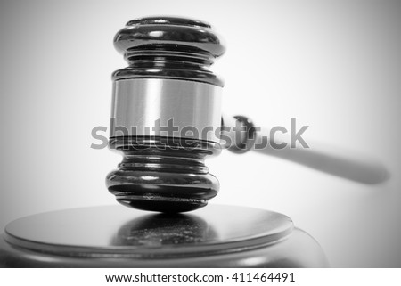 judge gavel over a grey background in black and white / judge gavel