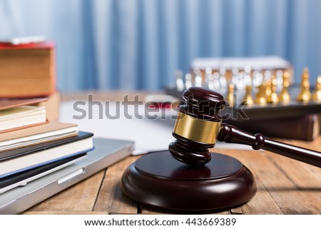 Judge gravel close up lawyer desk workplace, laptop, tablet, law book, golden chess checkers for legislation concept. - stock photo