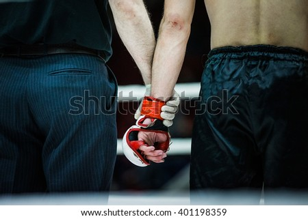 judge holds hand of boxer before announcing winners in ring - stock photo