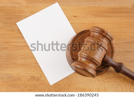 Judge's gavel and blank paper on wooden table - stock photo