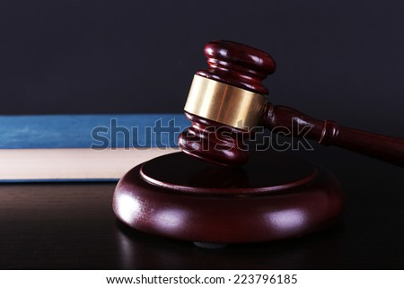 Judge's gavel and blue book on dark grey background - stock photo