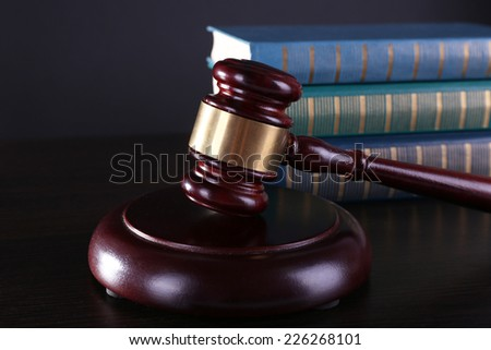 Judge's gavel and books on dark grey background