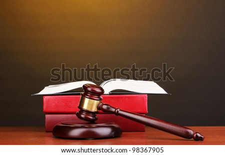 Judge's gavel and books on wooden table on brown background - stock photo