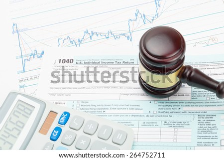Judge's gavel and calculator over 1040 US Tax form - stock photo