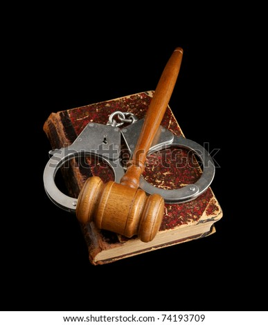 Judge's gavel and handcuffs on old legal book isolated - stock photo