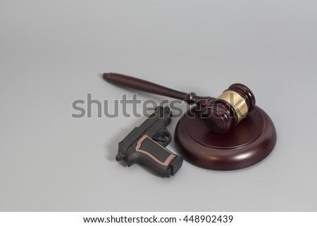 judge's gavel and handgun  isolated on gray background - stock photo