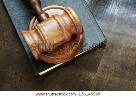 Judge's gavel and legal book on wooden table - stock photo