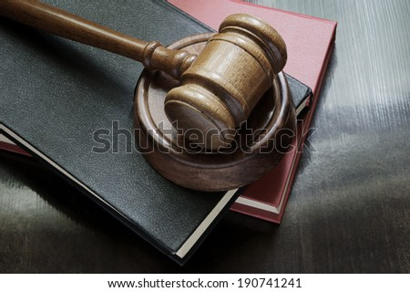 Judge's gavel and legal books on wooden table - stock photo