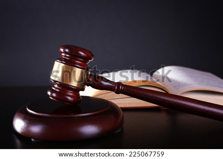 Judge's gavel and open book on dark grey background - stock photo