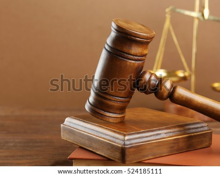 Judge's gavel and scales on brown background