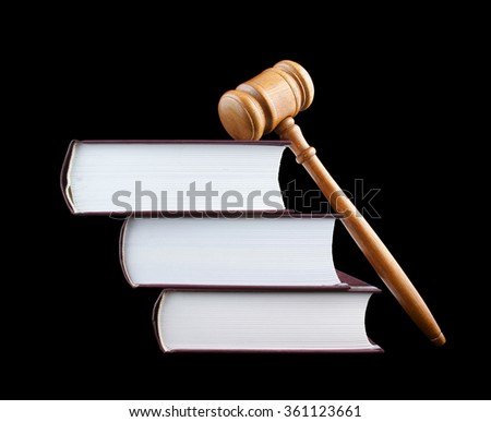 Judge's gavel and stack of legal books isolated on black - stock photo