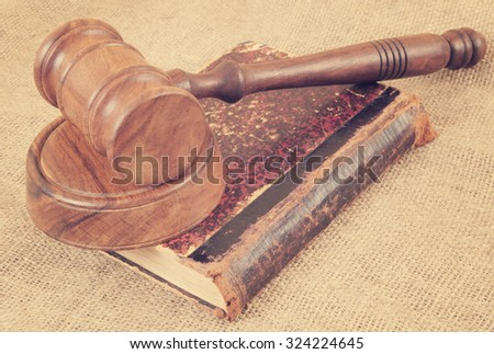 Judge's gavel and very old legal book on jute background - stock photo