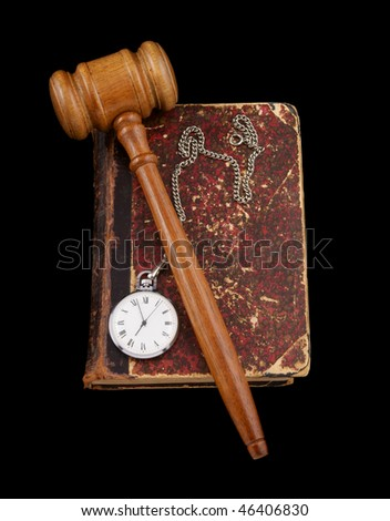 Judge's gavel and very old legal book with watch isolated on black - stock photo
