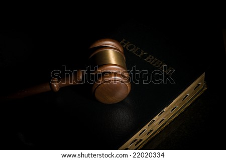Judge's gavel laying on top of a black holy Bible - stock photo